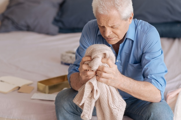 Sad unhappy senior man sitting in the bedroom and holding his wifes knitted jacked while grieving about her