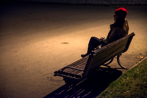 Sad unhappy woman sitting on bench in loneliness and looking away. stressed woman in a night time