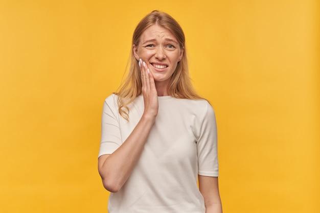 그녀의 뺨을 만지고 노란색에 치통을 갖는 흰색 티셔츠에 주근깨가있는 슬픈 불행한 여자