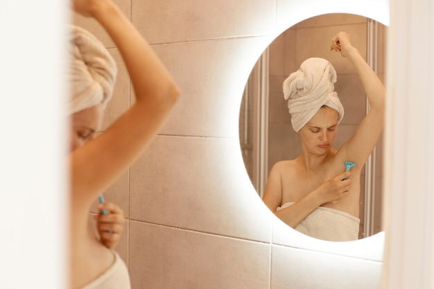 Sad unhappy young adult woman shaving armpit in bathroom, looking at her body, depilation process, attractive female with bare shoulders and wrapped in white towel.