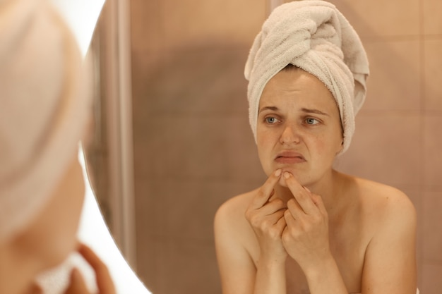 Sad unhappy young adult woman wearing bath towel squeezing acne on chin, mirror reflection of female with pimples on her face, skin problems, skin care.
