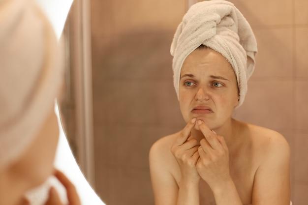 あごににきびを絞るバスタオルを身に着けている悲しい不幸な若い大人の女性、彼女の顔ににきびを持つ女性の鏡の反射、皮膚の問題、スキンケア。