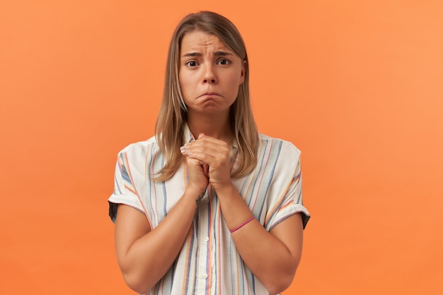 Sad unhappy young woman in casual clothes keeps hands in praying position and looking at front isolated over orange wall