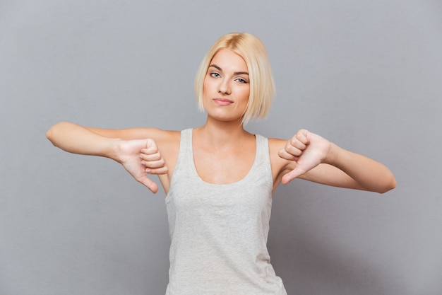 Sad unhappy young woman showing thumbs down with both hands over gray wall