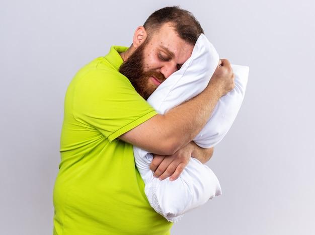 L'uomo triste e malsano con la barba in polo gialla si sente male tenendo il cuscino vuole dormire in piedi sul muro bianco