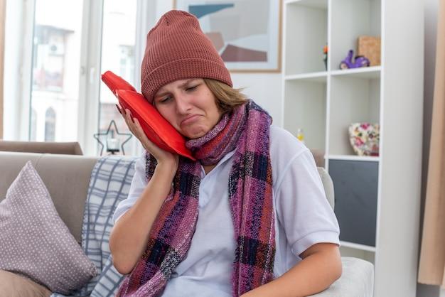 목 주위에 따뜻한 스카프가 달린 모자에 슬픈 건강에 해로운 젊은 여성이 가벼운 거실에서 소파에 앉아 입술을 움켜 쥐고 감기와 독감으로 고통 받고 아픈 느낌