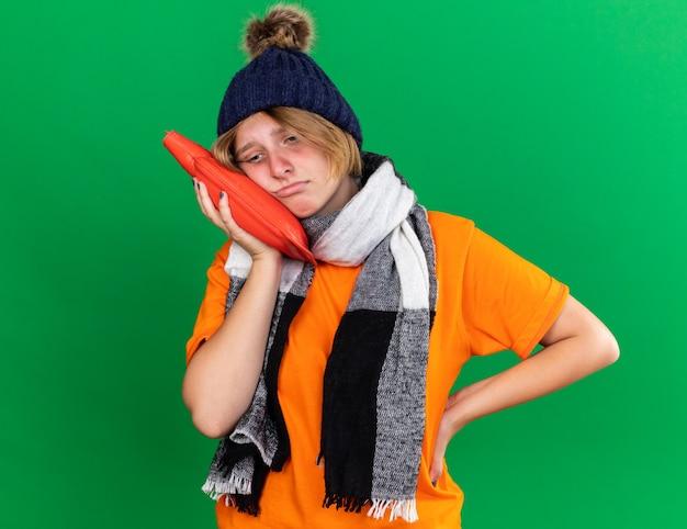 Triste giovane donna malsana in t-shirt arancione con cappello e sciarpa calda intorno al collo sensazione terribile con una borsa dell'acqua calda che soffre di freddo