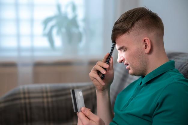 彼の携帯電話を保持し、ブロックされた悲しい動揺怒っている少年若いイライラしたストレスの心配した男