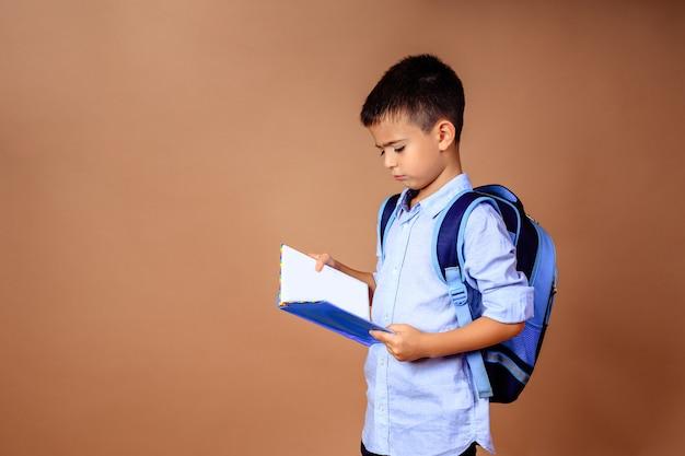 Печальный расстроенный мальчик-школьник с книгой в руках на бежевом фоне