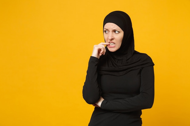 Sad upset crying confused young arabian muslim woman in hijab black clothes posing isolated on yellow wall, portrait. people religious islam lifestyle concept.