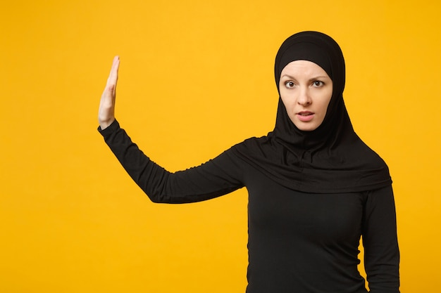 Sad upset crying confused young arabian muslim woman in hijab black clothes posing isolated on yellow wall  portrait. people religious islam lifestyle concept.