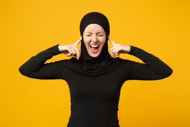 黄色の壁、肖像画に隔離されたポーズをとってヒジャーブの黒い服を着た若いアラビアのイスラム教徒の女性を混乱させて泣いて悲しい動揺。人々の宗教的なイスラムのライフスタイルの概念。