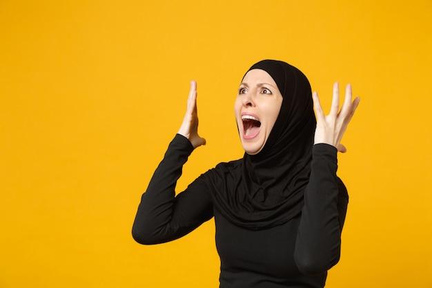 노란색 벽, 초상화에 고립 된 포즈 hijab 검은 옷에 슬픈 화가 우는 젊은 아라비아 무슬림 여성 혼란. 사람들이 종교 이슬람 라이프 스타일 개념.