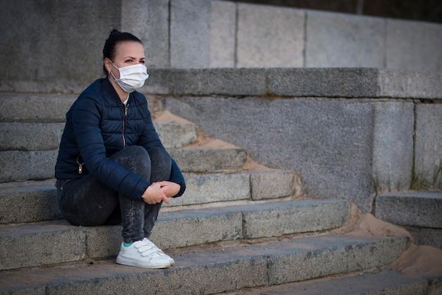 悲しい動揺して落ち込んでいる女の子、階段の上に座っている孤独な欲求不満な若い女性、隔離のために苦しんでいる、コロナウイルス。顔に医療用防護マスクの人。失恋、ウイルス、流行のコンセプト