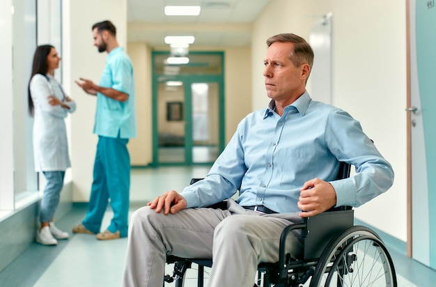 A sad, upset elderly disabled person in a wheelchair sits in the middle of a clinic corridor waiting for his family, with doctors behind him.