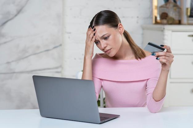 悲しい動揺イライラした神経質な女の子、若い怒っている不幸な女性がブロックされたクレジット銀行カードを保持しています