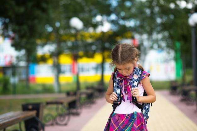 バックパックを持って学校の近くで悲しい、動揺した女の子。クラスからの疲労、恨み、