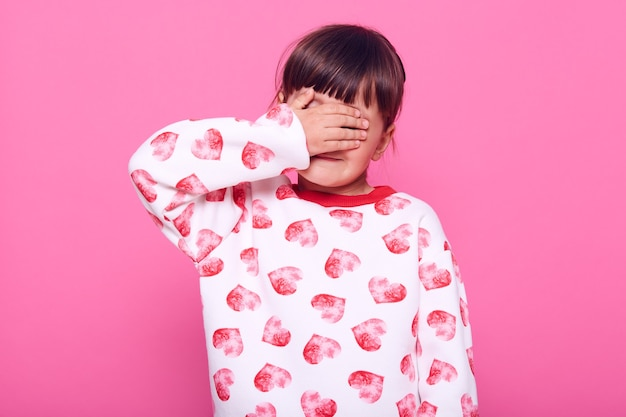 Sad upset little girl has bad news, crying, covering her eyes with palm, wearing white sweater with hearts print, isolated over pink wall.