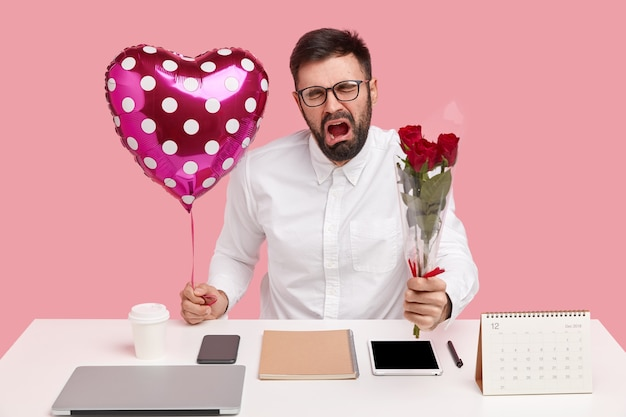 L'uomo triste e sconvolto riceve il rifiuto dal collega fino ad oggi, porta un mazzo di rose, san valentino, piange di disperazione, vestito con un'elegante camicia bianca