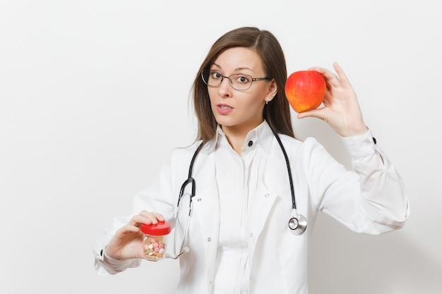 Унылая расстроенная женщина довольно молодого доктора со стетоскопом, очками, изолированными на белом фоне. женщина-врач в медицинском халате держит бутылку с таблетками, красное яблоко. медицинский персонал, концепция медицины.