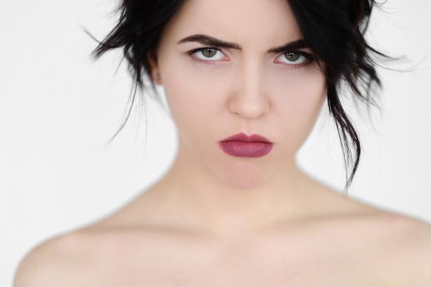 Грустная расстроенная серьезная женщина с угрюмым взглядом на белой стене.