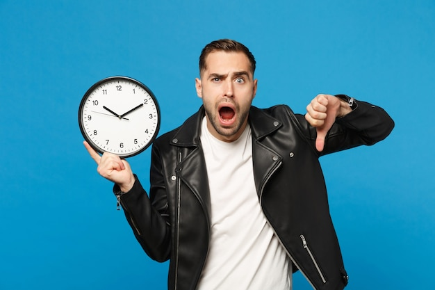 Sad upset stylish young unshaven man in black leather jacket white t-shirt holding round clock isolated on blue wall background studio portrait. people lifestyle concept. hurry up. mock up copy space.
