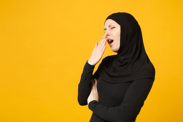 Sad upset tired confused young arabian muslim woman in hijab black clothes posing isolated on yellow wall  portrait. people religious islam lifestyle concept.