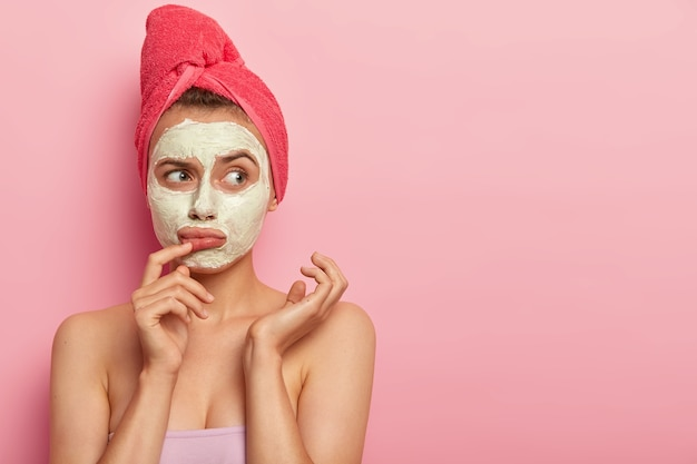 Sad upset woman wears white natural mask, has thoughtful expression, wants to have glow perfect smooth skin, applies facial clay mask, towel on head