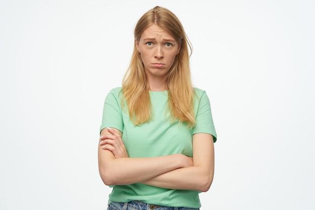 ミントのtシャツにそばかすのある悲しい動揺した女性は腕を組んで、白で気分を害しているように見えます