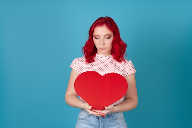 Sad, upset  woman with red hair holds a large red paper heart