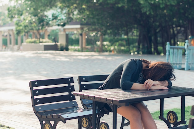 A sad, upset and worried woman sitting down alone outdoors