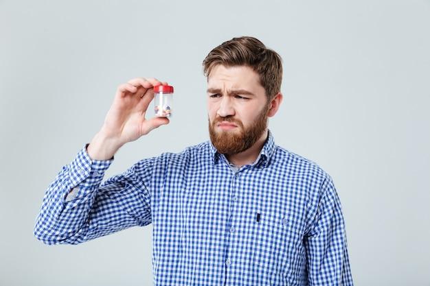 Грустный расстроенный молодой человек держит и смотрит на бутылку таблеток над белой стеной