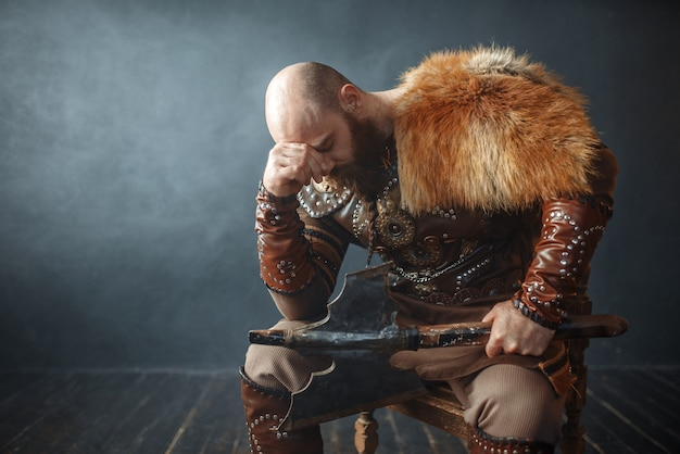 Sad viking with axe sitting on chair