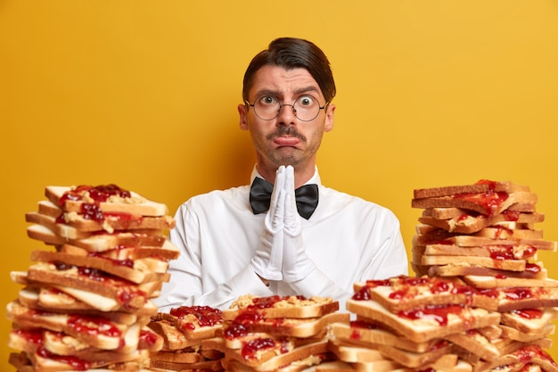 Sad waiter has pleading expression, feels sorry for doing something wrong, dressed in uniform, works in luxury restaurant, surrounded by pile of bread snacks, poses against yellow wall.