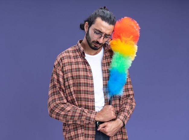 青い壁にコピー スペースで隔離された羽毛ダスターを保持している t シャツを着た若いハンサムな掃除男が目を閉じて悲しい