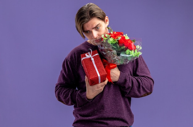 Sad with lowered head young guy on valentines day holding gift box with bouquet isolated on blue background