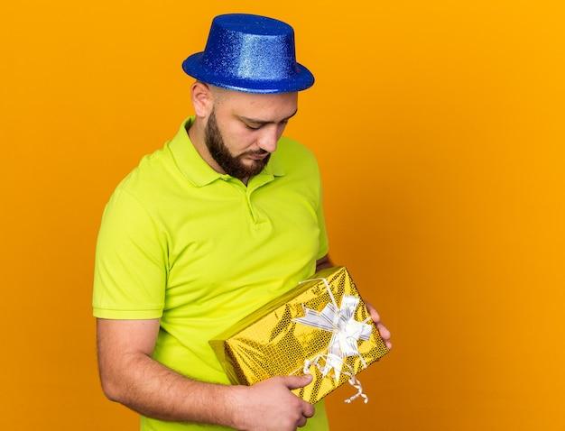 オレンジ色の壁に分離されたギフトボックスを保持しているパーティーハットを身に着けている頭を下げた若い男と悲しい
