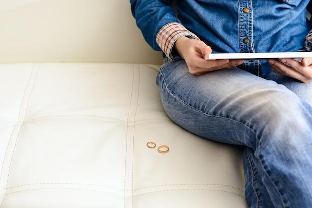 部屋のソファーの近くの床に座っているフレームで家族の写真を見て、離婚後の悲しい女。離婚の概念