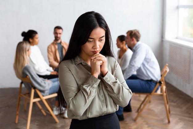 椅子に座っている人々との集団療法セッションで悲しい女性