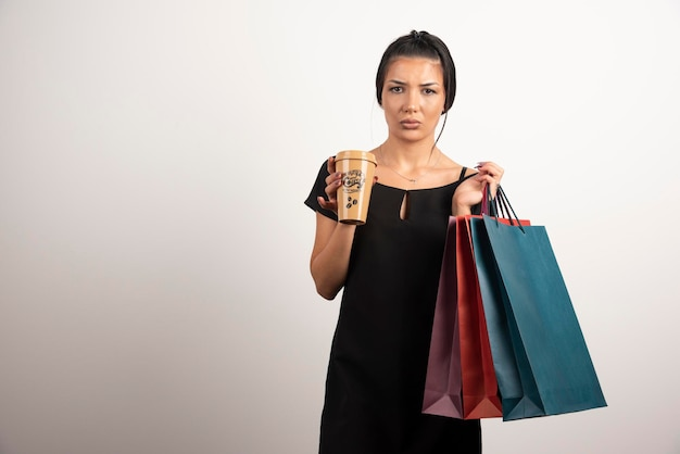 Sad woman carrying shopping bags and coffee on white wall.