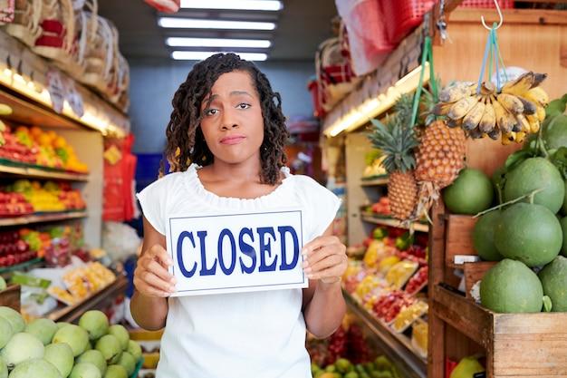Sad woman closing store