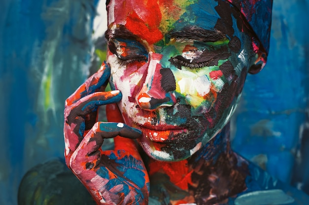Sad woman covered with multicolored paint
