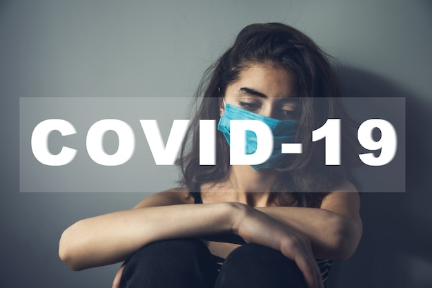 Sad woman and covid-19 text in screen
