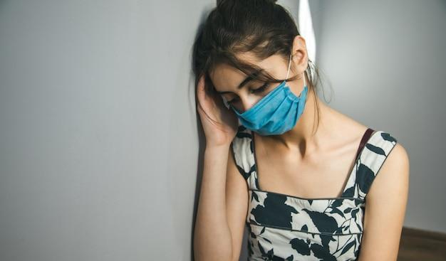Грустная женщина маска для лица на серой стене