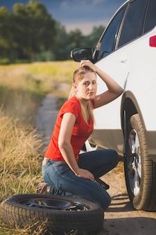 悲しい女性は、フィールドでパンクしたタイヤを交換することについて混乱しました