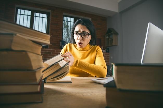 悲しい女性はテーブルにたくさんの本を手渡します