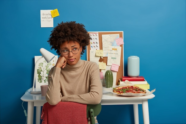 Sad woman has afro haircut sits at chair, wears round spectacles and beige jumper, sits in coworking space, table with notes desk lamp and delicious pizza behind.