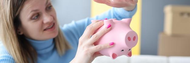 ピンクの貯金箱のクローズアップで彼女の手を打つ悲しい女性