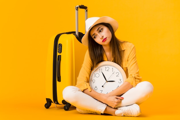 Sad woman holding clock and posing next to luggage
