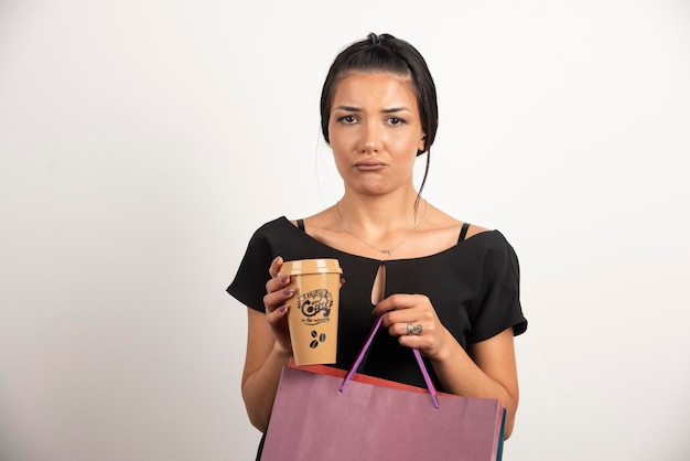 Sad woman holding coffee and shopping bags on white wall.